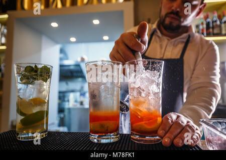 Barman verse de l'eau pétillante dans cocktail Banque D'Images