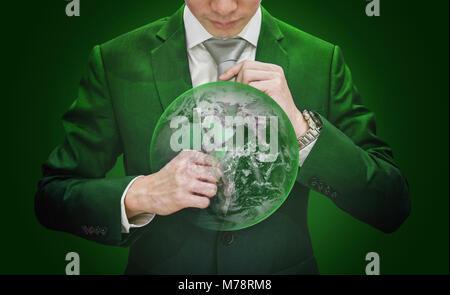 Homme d'affaires en costume cravate verte holding avec Green Globe, sur fond vert. Élément de cette image sont meublées Banque D'Images