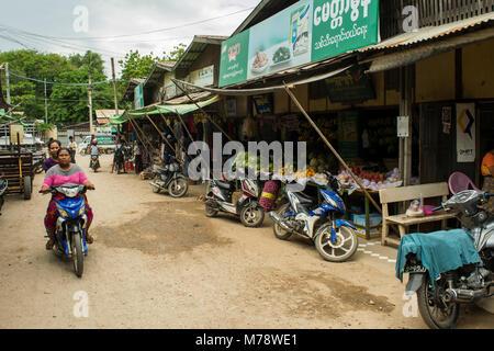 Deux femmes birmanes sur une moto bike roulant en Nyaun local U marché plein air à côté de fruits et légumes, Bagan Banque D'Images