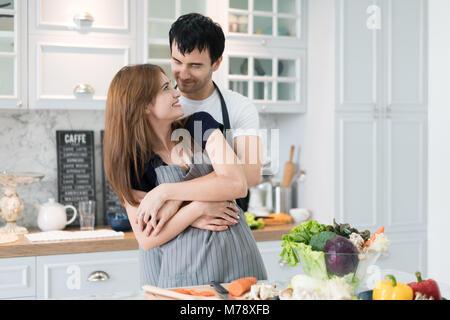 Jeune couple charmant la préparation de repas sain dans la cuisine moderne. Man hugging woman romantique de matin Banque D'Images