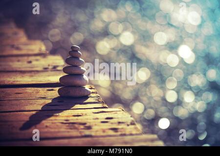 La paix intérieure et l'équilibre, tas de cailloux sur le pont de bois sur la plage, les vacances d'été sur la station Banque D'Images