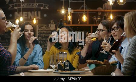 Groupe diversifié d'amis célébrer avec un toast et de Clink soulevées Lunettes avec diverses boissons dans la célébration. Banque D'Images