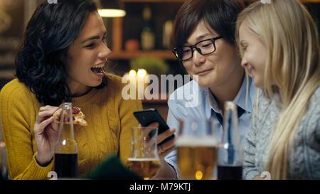 Groupe varié de jeunes s'amuser en Bar, parler, raconter des histoires et des blagues. Ils boivent des boissons Banque D'Images