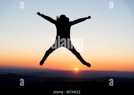 Une jeune femme montre des gestes joyeux dans le soleil couchant de Dartmoor, Royaume-Uni. Banque D'Images