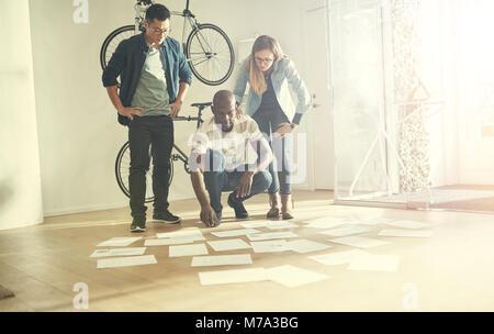 Trois jeunes collègues d'affaires debout dans un bureau moderne et élégante de la paperasserie de lecture portant Banque D'Images
