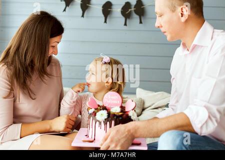 Les parents avec un peu jolie fille. Girl essaie le gâteau avec son doigt Banque D'Images