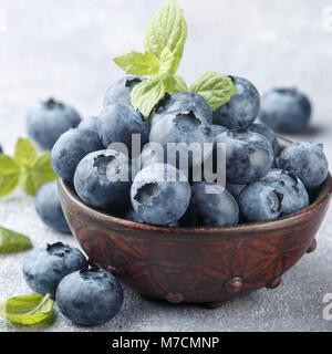 Les bleuets frais biologiques dans une cuvette d'argile. Petits fruits juteux et de feuilles de menthe sur une pierre Banque D'Images