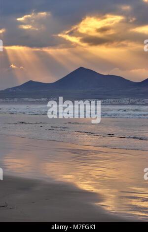 Playa de Famara, Lanzarote, îles Canaries, Espagne. Vue de soo au coucher du soleil avec ciel reflétées sur beach Banque D'Images