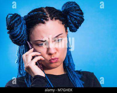 Belle jeune femme en colère avec tresses bleu africains parler sur son téléphone. Portrait de jeune fille à la mode Banque D'Images