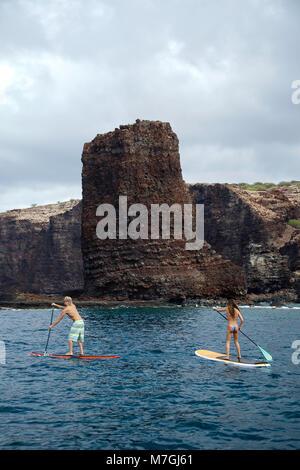 Un jeune couple sur le stand-up paddle boards à aiguilles à l'extérieur de l'île de Lanai, Hawaii. Les deux sont Banque D'Images