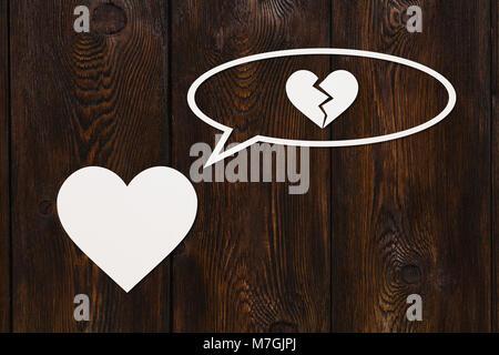Coeur de papier est de penser à une rupture sur fond de bois. Image abstrait Banque D'Images