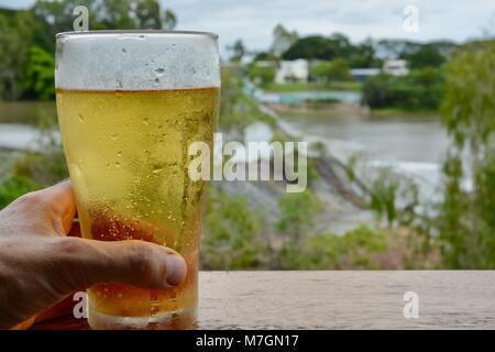 Boire une bière avec vue sur l'eau de déborder la Weir après de fortes pluies récentes, Riverview Taverne dans Douglas Banque D'Images