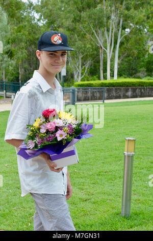 Jeune homme sur une planche à roulettes portant un bouquet de fleurs pour l'anniversaire de sa grand-mère, Riverview Banque D'Images