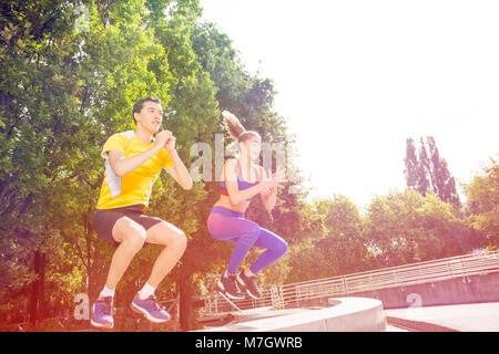 Les personnes actives faisant fort aller au cours de l'exercice d'entraînement Crossfit extérieur en été Banque D'Images