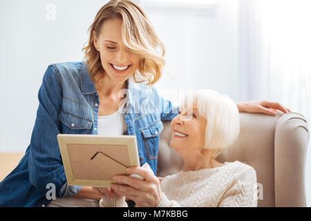 Cheerful âgés de femme en riant et montrant une photo de sa petite-fille Banque D'Images