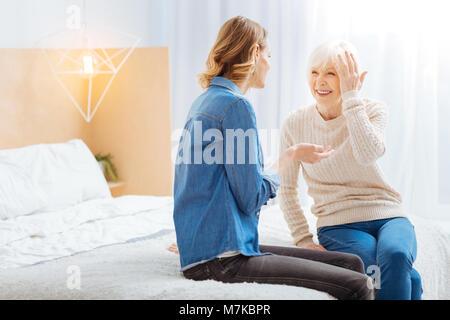 Senior woman looking at sa petite-fille et rire de sa plaisanterie drôle Banque D'Images