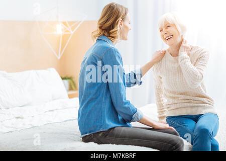 Femme âgée émotionnel touchant son cou en riant Banque D'Images