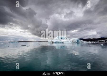 Nuages spectaculaires reflétées dans l'eau glacée de la glacier Vatnajokul prises à partir d'un bateau sur le lac Banque D'Images