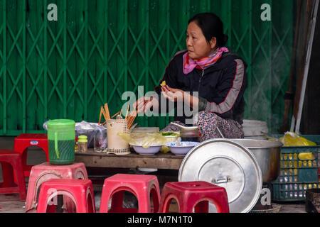 Une femme attend pour les clients à son restaurant d'aliments de rue improvisé à Hue, Vietnam. Les femmes ont tout Banque D'Images