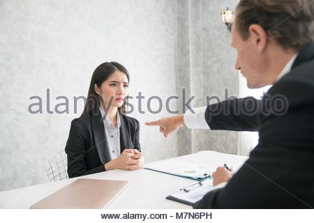 Leader de l'entreprise coupable de pointage courroucée employée à la sortie et lui demander de quitter, peur du Banque D'Images