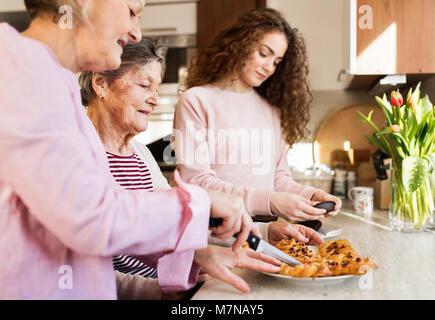 Une adolescente avec mère et grand-mère à la maison. Banque D'Images