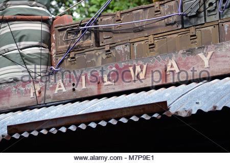 L'ancien panneau en bois de fer avec écrit dessus. Sous le toit en tôle ondulée et assurance stockés au-dessus. Banque D'Images