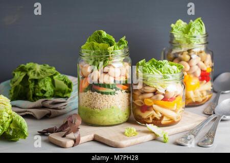 Salade de pâtes et de couscous végétalien dans des pots Mason avec haricots Légumes Banque D'Images