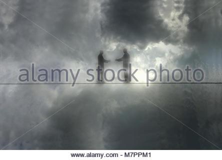 Deux hommes d'atteindre pour serrer la main sur la corde raide dans le brouillard Banque D'Images