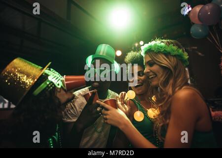 Groupe de multi-ethnic friends having fun at bar. Sourire les hommes et les femmes à faire la fête et célébrer le Jour de la Saint Patrick en discothèque.