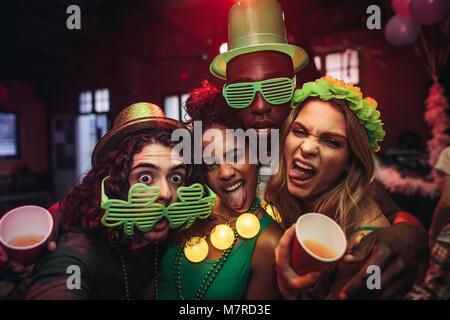 Crazy jeunes amis profitant d'une partie au pub. Les hommes et les femmes dans le trèfle vert partie lunettes et chapeau de leprechaun at night club. Les gens célébrant St.Patri