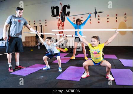 Un jeune garçon et fille et mère de soulever une barre de poids sous la supervision d'un instructeur de Fitness. Banque D'Images