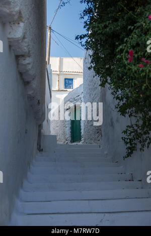 Escaliers dans les rues étroites de Chora d'Amorgos avec une porte verte en haut et une fenêtre bleue Banque D'Images