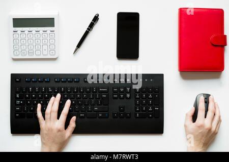 Vue de dessus, woman sitting at desk et travaillant sur son pc, sa table est parfaitement bien rangé et organisé Banque D'Images