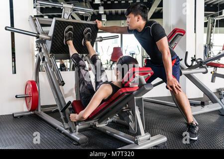 Sportive femme brune à l'aide de poids Appuyez sur la machine pour les jambes avec l'aide de son entraîneur personnel Banque D'Images