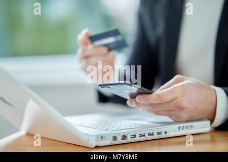 Man looking at laptop holding credit card