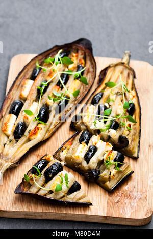 Aubergine farcis de Feta et olives noires sur fond noir en noir Banque D'Images