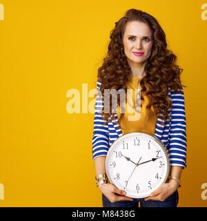 Jeune femme en blouson rayé sur fond jaune avec horloge Banque D'Images