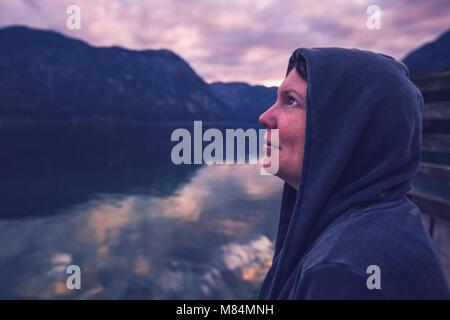 Lonely Woman looking at ciel dramatique. Personne de sexe féminin in hoodie seul se tenant par le lac, les ombres Banque D'Images