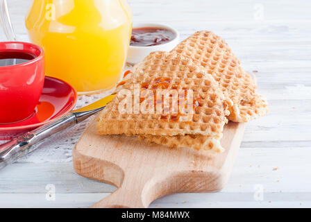 Des délicieux gaufres minces avec de la confiture, tasse de café, jus de fruits sur la table . Copier l'espace. Banque D'Images