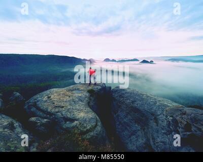 Photographe professionnel au-dessus des nuages. L'homme prend des photos avec l'appareil photo sur trépied sur piton Banque D'Images