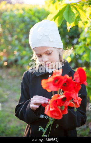... Belle petite fille en robe et chapeau holding bouquet de fleurs de  pavot rouge au printemps 64c32ff55a1