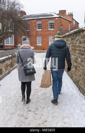 L'homme et de la femme marchant le long d'un chemin couvert de neige et de glace l'homme porte un sac de magasinage, Banque D'Images