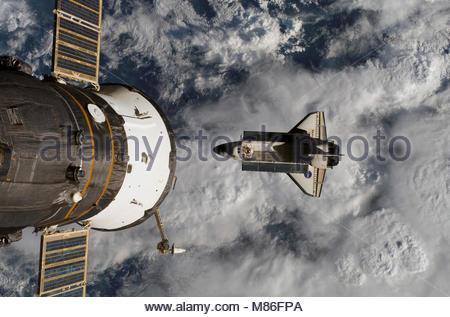 Le chemin de la maison. Backdropped couvertes de nuages par une partie de la Terre, la navette spatiale Atlantis Banque D'Images
