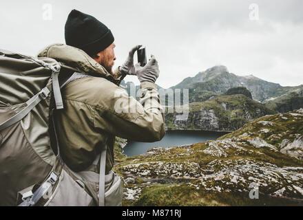 Man Traveler GPS Navigator smartphone contrôle randonnées en montagne en plein air concept de vie survie Voyage Banque D'Images