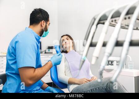 Dentiste parle au patient lors de l'enregistrement jusqu' Banque D'Images
