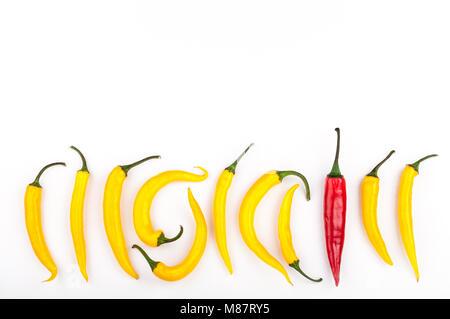 Piment rouge debout à partir de la foule de identique poivrons jaunes sur fond blanc. Le leadership, l'être unique, Banque D'Images