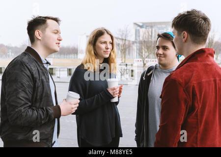 Groupe d'amis adolescents ayant une conversation tout en se tenant ensemble on city street Banque D'Images