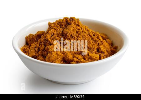 La poudre de curry dans un bol en céramique blanc isolé sur blanc. Banque D'Images
