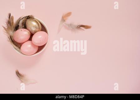 Rose et Or Oeufs de Pâques dans un bol. Pâques Oeufs Pastel Concept avec et de plumes. Punchy Pastels. Copy Space