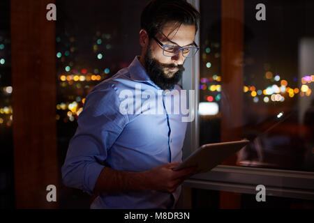 Young businessman looking at digital tablet in office at night Banque D'Images